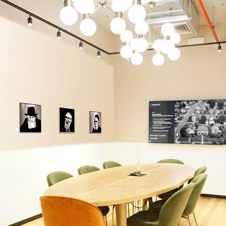 Jewish art in modern office with gedolim portraits